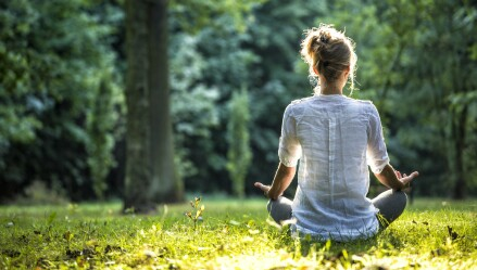 A woman meditates outdoors