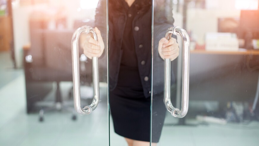 A photo of a woman opening two glass doors