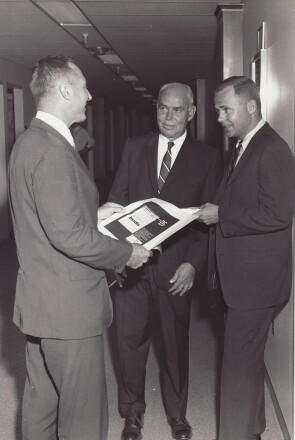 A young James Burke (far right) reviews an ad for Cotton Buds with colleagues