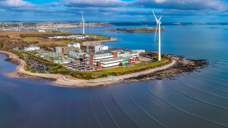 A photo of a production facility, including wind turbines, surrounded by water
