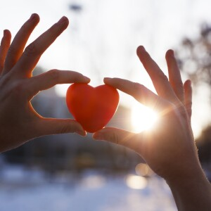 Hands holding up a red heart