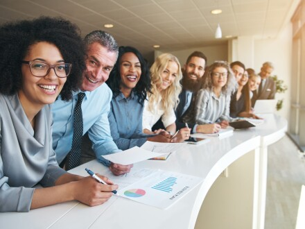 smiling group of diverse people sitting at a counter in an office
