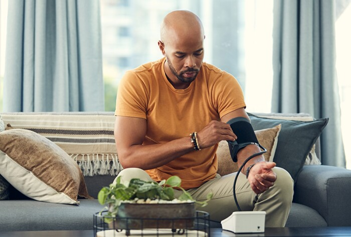Masculine presenting person, taking blood pressure reading at home.