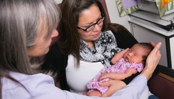 Lesley Paulette, an Indigenous registered midwife, with a mother and child in Canada