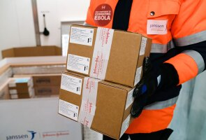 A worker carries a shipment of Janssen's investigational Ebola vaccine