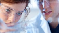 two young scientists look at something in a lab