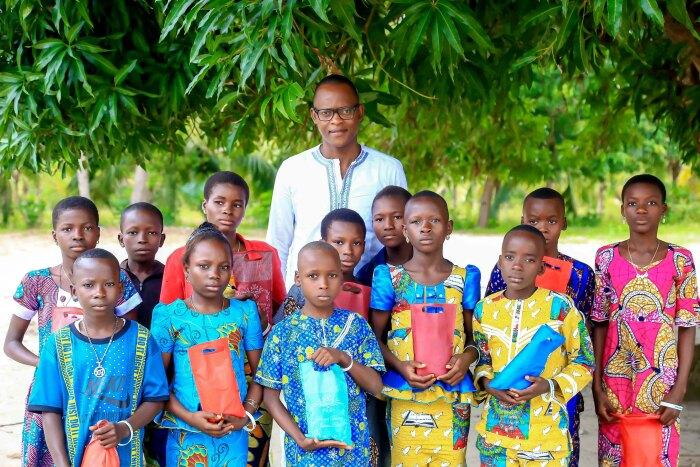 A photo of Philemon Padonou with CodeToHope children