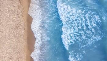 An overhead view of waves crashing on a beach