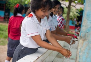 Young students practicing good hygiene & washing their hands at Institución Educativa Sarita Colonia
