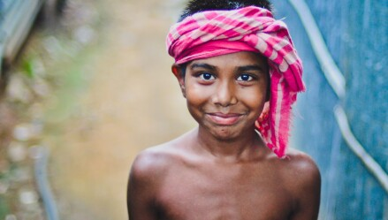 A photo of a boy with a scarf tied around his head