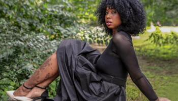 Feminine-presenting person, with psoriasis on legs, posing in dress outside, Alisha Bridges.